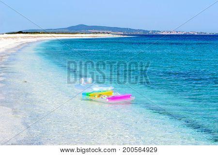 air mattress anchored in a desert paradise beach