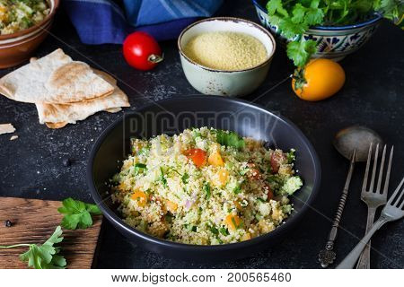 Lebanese arabic cuisine: healthy delicious salad with cous cous, fresh vegetables and greens called Tabbouleh in black bowl. Authentic cuisine