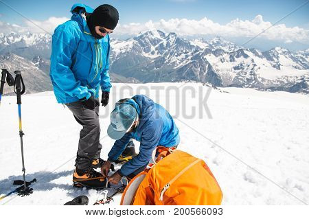 A professional guide helps you set up and dress alpinist crampons for a beginner mountaineer before climbing