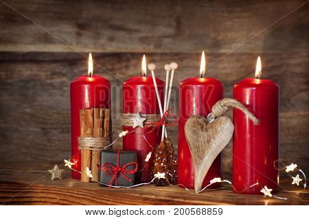 Still life with red advent candles and a little gift in front of a wooden background