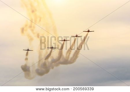 Group Of Fighter Jet Airplane With A Trace Of White Smoke Against A Blue Sky
