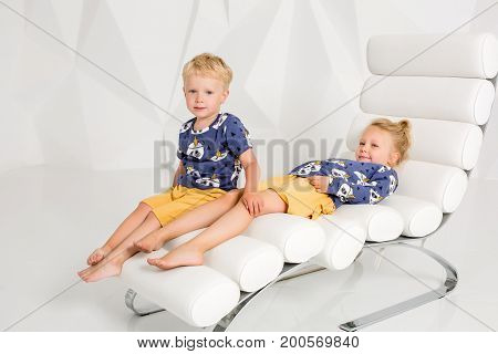 Portrait of the sister and its little brother at white studio. Little children are sitting on a white armchair