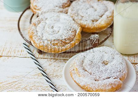 Traditional Spanish or Philippine pastry ensaimada. Powdered on cooling rack and plate. Glass of milk top view white wood background.