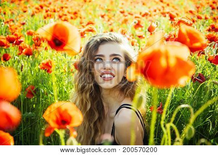 girl. long curly hair hold flower in field of red poppy seed with green stem on natural background summer spring drug and love intoxication opium