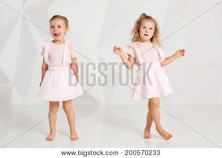 Two little funny and laughing girl in gently pink dresses posing in white studio. Beautiful little fashion models on white studio background