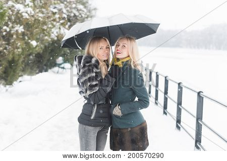 Two Sisters Smiling Under Umbrella On Winter Day