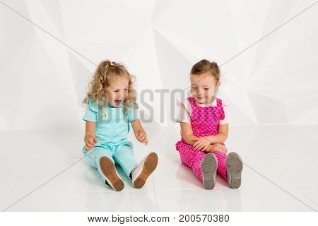 Two little girlfriends in the identical overalls of different colors sitting on the floor in a studio with white walls. Little girls posing on camera