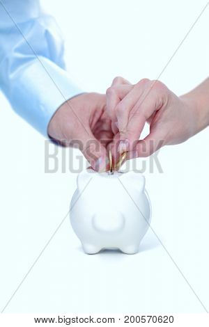 A hand hold a coin into the pig coin bank money box isolated white background