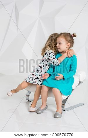Two little girlfriends in the identical dresses of different colors sitting on a chair in a studio with white walls. Little girls posing on camera