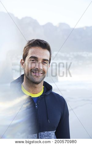 Smiling man in hooded top on beach portrait