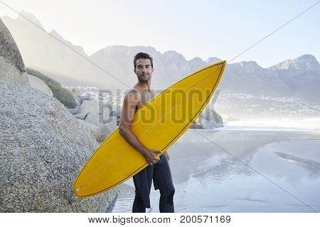 Surfer dude standing on beach looking at camera