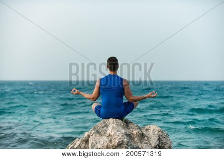 Man practicing yoga. Boy meditating on stone. harmony and relaxing concept. yogi sitting in lotus pose near blue ocean. healthy body and soul