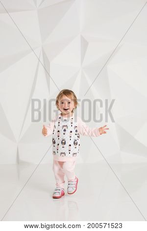 Year-old child standing near white wall in studio. Portrait of cute girl posing in studio.