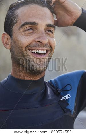 Laughing guy with stubble on beach close up