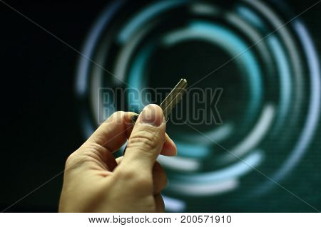 hand holding Key in front of a computer screen. key to power and success concept