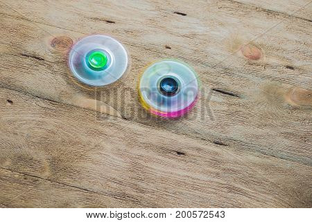 Colored Fidget Spinners Stress Relieving Toy On Wooden Background