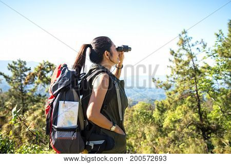 Women hiker with backpack checks map to find directions and look binoculars in wilderness area at mountain and forest. Travel Concept
