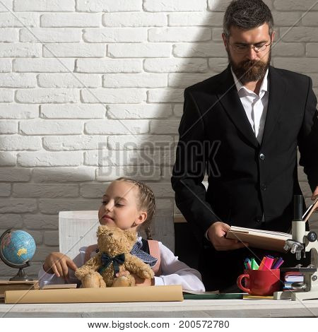 Schoolgirl And Dad With Busy Faces Hold Bear And Book