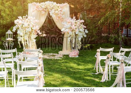 Wedding arch decorated with cloth and flowers outdoors. Beautiful wedding set up. Wedding ceremony on green lawn in the garden. Part of the festive decor, floral arrangement