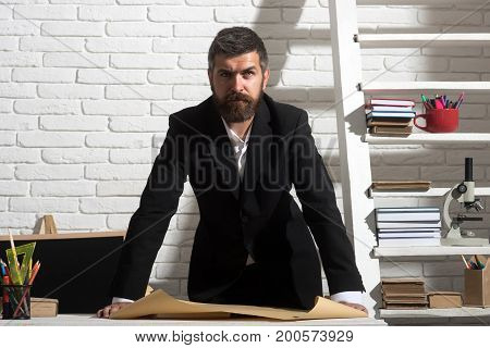 Professor With Serious Face Expression Stands By Desk With Paper