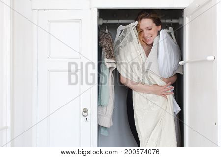 A woman is overwhelmed in a closet of messy clothes for a style or fashion concept.