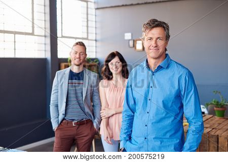 Portrait of a confident mature businessman standing in a modern office with two smiling work colleagues standing in the background
