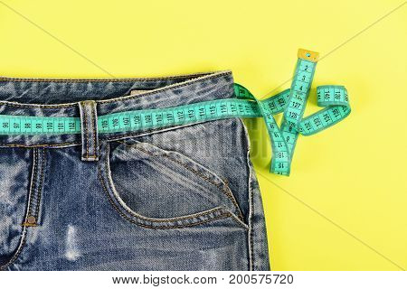 Healthy lifestyle and dieting concept. Upper part of denim trousers isolated on yellow background. Close up of jeans with measure tape around waist. Blue jeans with blue measure tape instead of belt.