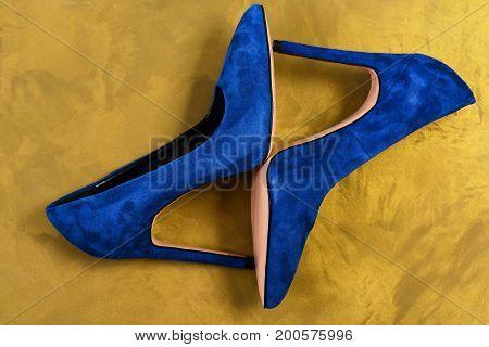 Blue High Heel Shoes On Golden Texture Background