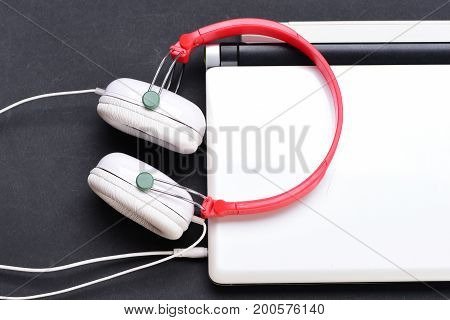 Music And Digital Equipment Concept. Headphones And Silver Laptop