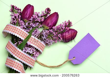 Tulips and lilac flowers in bunch with purple price tag isolated on light background top view and copy space. Concept of secret note and spring blossom