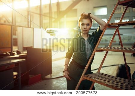 Portrait of modern young woman in green uniform working in engineering standing by jet plane near the stairs looking at camera.