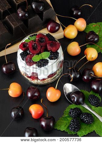 Oatmeal with yogurt and berries in a jar surrounded by cherries and blackberries