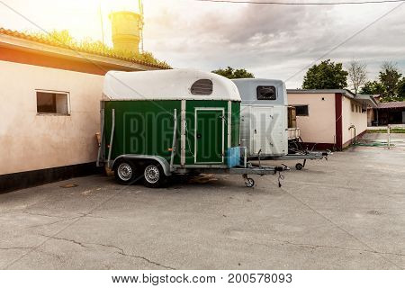 Special built trailer for transporting animals such as camels and horses. Standing on the parking near farm