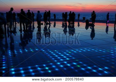 Silhouettes of humans in various activities upon a sunset background with reflections on solar panels on the ground forming a beautiful human symphony