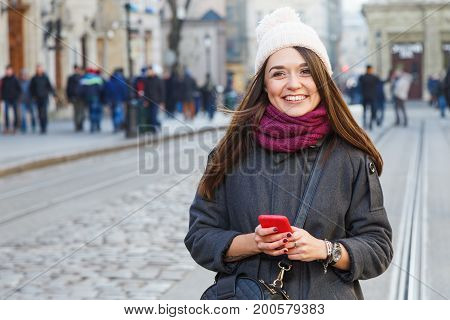 Positive Stylish Girl Holding Red Smart Phone On The Street