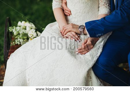 Bride and groom holding hands outdoors daylight