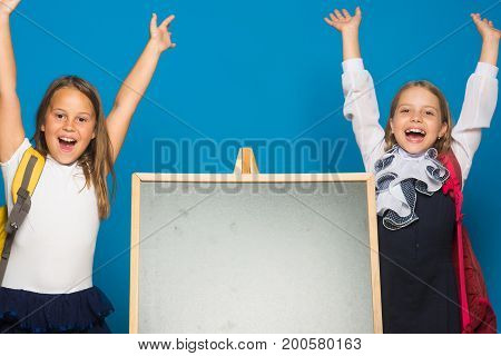 Schoolgirls With Happy Faces Stand Near Blackboard