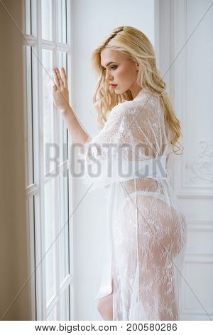 Beautiful sexy lady in elegant white robe. Close up fashion portrait of model indoors. Beauty blonde woman. Attractive body in lace lingerie. Female ass in underwear. Closeup fashionable naked girl