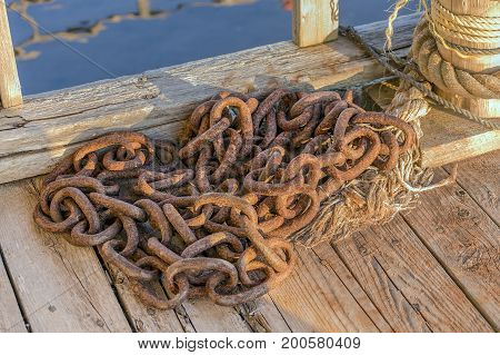 Heavy Rusty Chain Beside Post With Frayed Rope On Nautical Dock