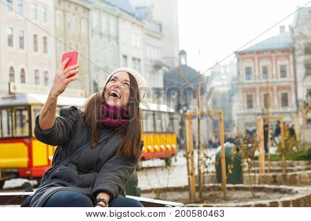 Young Brunette Woman Laughing With Smart Phone