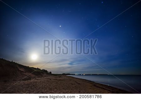 Full Moon Behind Soft Clouds Glowing And Casting Light On Beach At Night