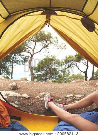 view from inside a tent at the forest and female legs emerge from tent. travel and hiking concept. Tourist tent inside with women's feet.