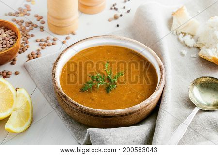 Bowl of delicious lentil soup with bread and lemon slice on a white wooden table. Traditional healthy vegetarian food. Top view.