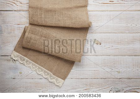 burlap hessian sacking on white wooden table top view