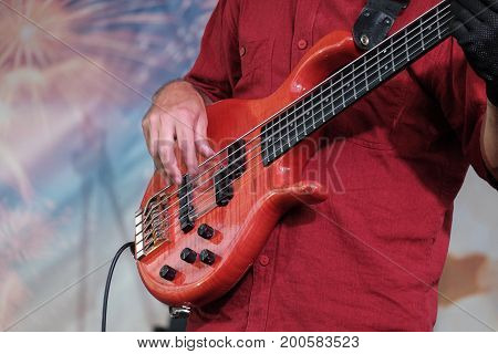 male musician in a red shirt plays a five-string bass guitar on stage
