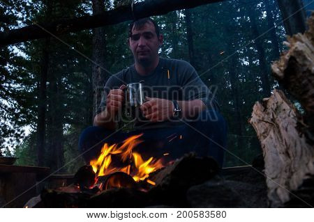 Young Man Sitting And Drinking Tea While Looking At Fire
