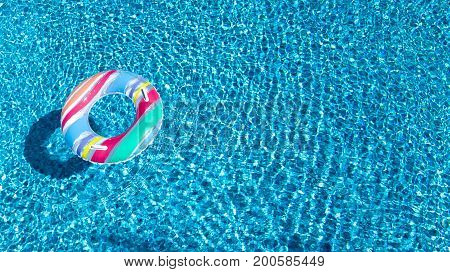 Aerial view of colorful inflatable ring donut toy in swimming pool water from above, family vacation concept background