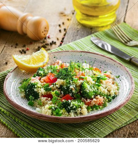 Plate with couscous and vegetables on a rustic wooden table. Traditional eastern healthy meal made of couscous broccoli tomato pepper onion and dill.