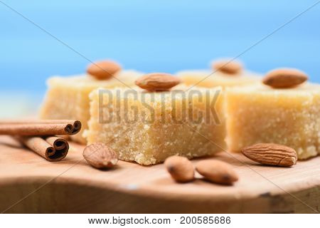 Traditional Indian dessert halava with almonds on wooden board closeup side view