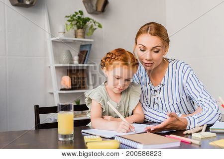 Mother And Daughter Drawing In Album